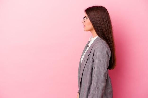 Молодая кавказская бизнес-леди, изолированная на розовой стене, глядя влево, боком представляет.