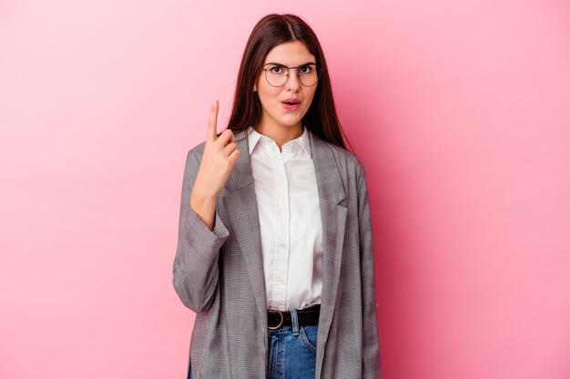 Молодая кавказская бизнес-леди изолирована на розовой стене, имея отличную идею, концепцию творчества.
