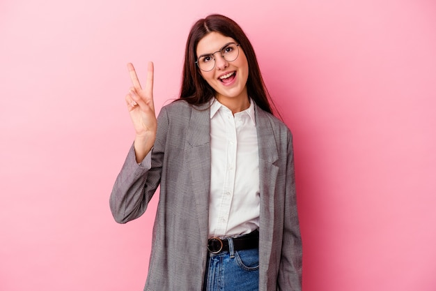 손가락으로 평화의 상징을 보여주는 즐겁고 평온한 분홍색 벽에 고립 된 젊은 백인 비즈니스 여자