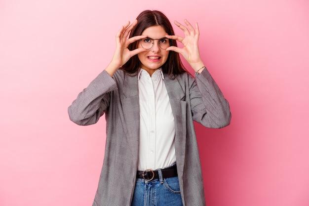Молодая кавказская бизнес-леди изолирована на розовой стене, держа глаза открытыми, чтобы найти возможность успеха.
