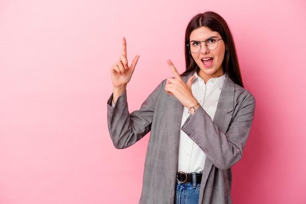 Молодая кавказская бизнес-леди изолирована на розовой стене, указывая указательными пальцами на копию пространства, выражая волнение и желание.
