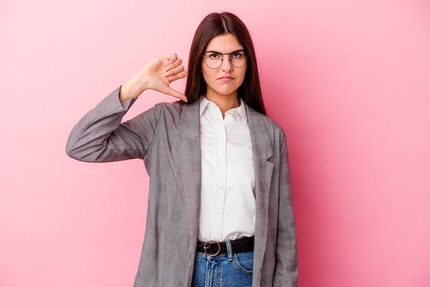 Молодая кавказская деловая женщина изолирована на розовой стене, показывая жест неприязни, пальцы вниз