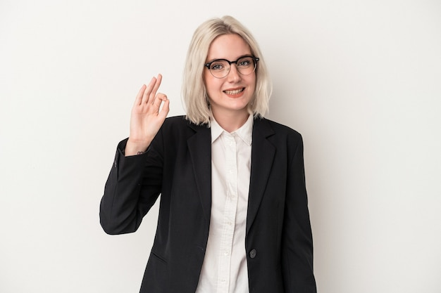 白い背景に分離された若い白人ビジネス女性は、陽気で自信を持って大丈夫なジェスチャーを示しています。
