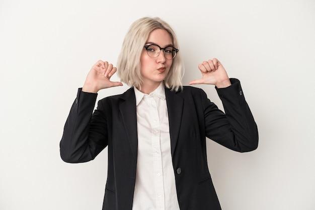 白い背景に隔離された若い白人のビジネス女性は、誇りと自信を持って、従うべき例を感じます。