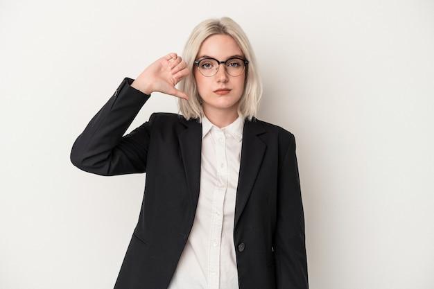 嫌いなジェスチャーを示す白い背景で隔離の若い白人ビジネス女性、親指を下に。不一致の概念。