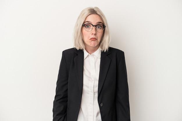 白い背景で隔離の若い白人ビジネス女性は肩をすくめ、目を開けて混乱します。