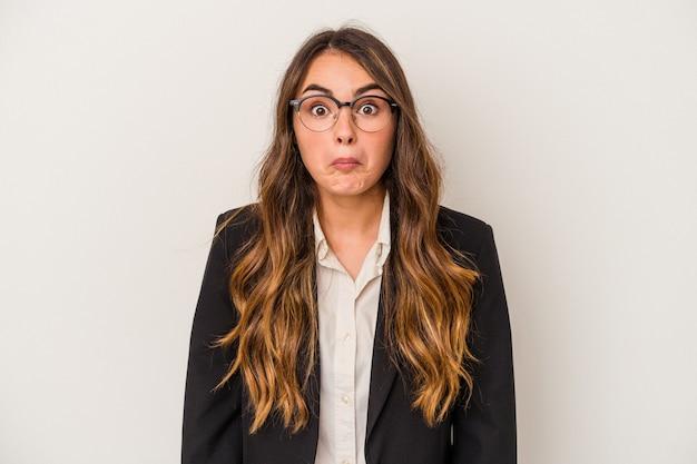 白い背景で隔離の若い白人ビジネス女性は肩をすくめると混乱した目を開いています。