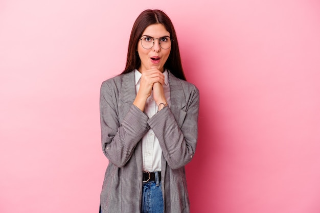 Young caucasian business woman isolated on pink background praying for luck, amazed and opening mouth looking to front.