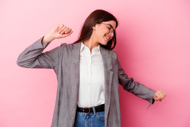 Young caucasian business woman isolated on pink wall dancing and having fun.