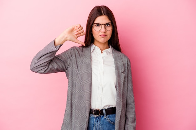Young caucasian business woman isolated on pink wall showing a dislike gesture, thumbs down
