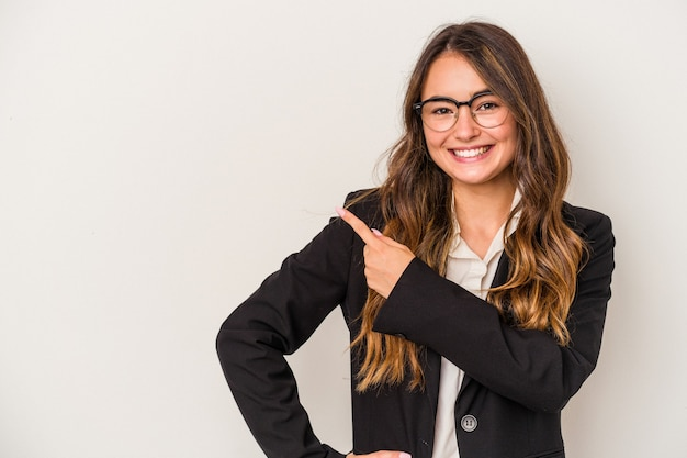 Young caucasian business woman isolated on white background smiling and pointing aside, showing something at blank space.