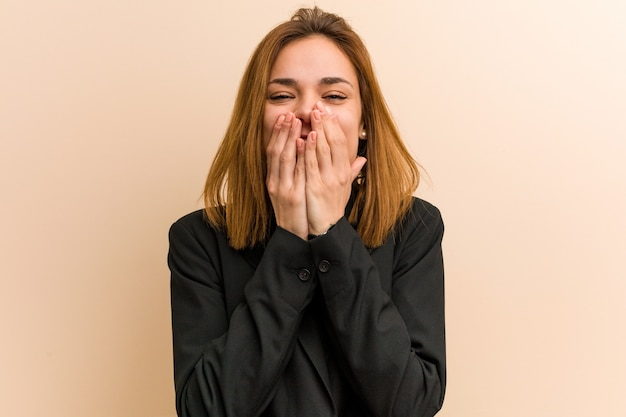Young caucasian business woman laughing about something, covering mouth with hands.