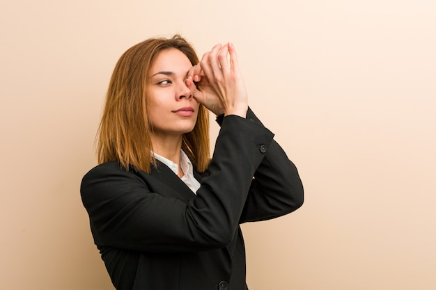 Young caucasian business woman looking far away keeping her hand on forehead.