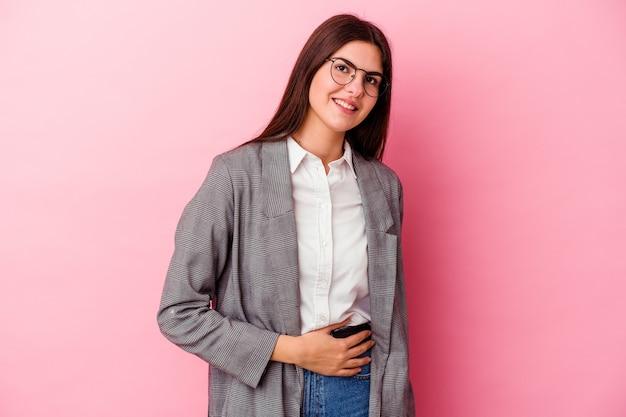 Молодая кавказская бизнес-леди на розовом трогает животик, нежно улыбается, ест и удовлетворение концепции.