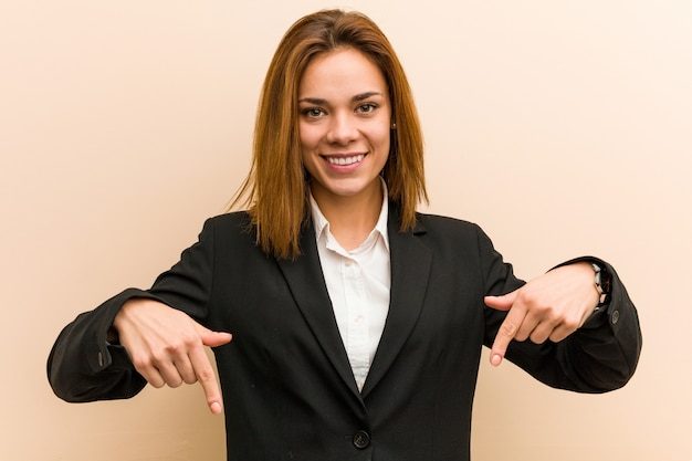 Young caucasian business woman points down with fingers, positive feeling.