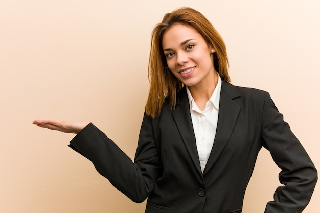 Young caucasian business woman showing a copy space on a palm and holding another hand on waist.