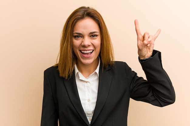 Young caucasian business woman showing a horns gesture