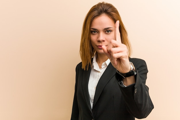 Young caucasian business woman showing number one with finger.