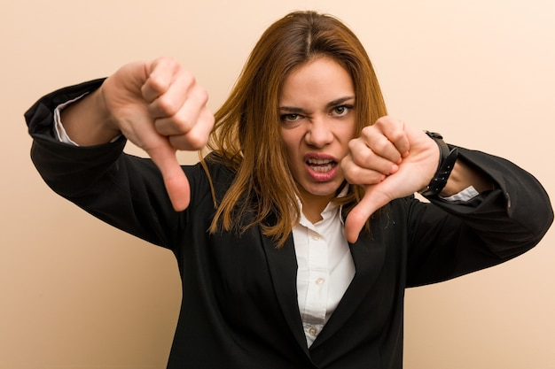 Young caucasian business woman showing thumb down and expressing dislike.