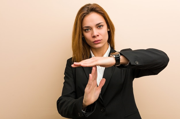 Young caucasian business woman showing a timeout gesture.