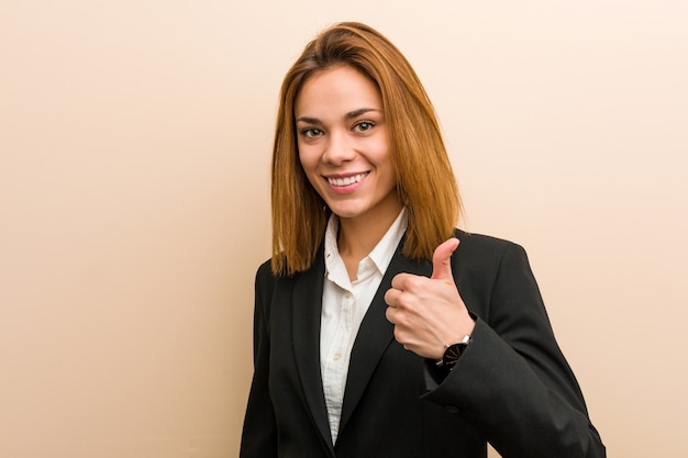 Young caucasian business woman smiling and raising thumb up