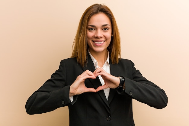 Young caucasian business woman smiling and showing a heart shape with her hands.