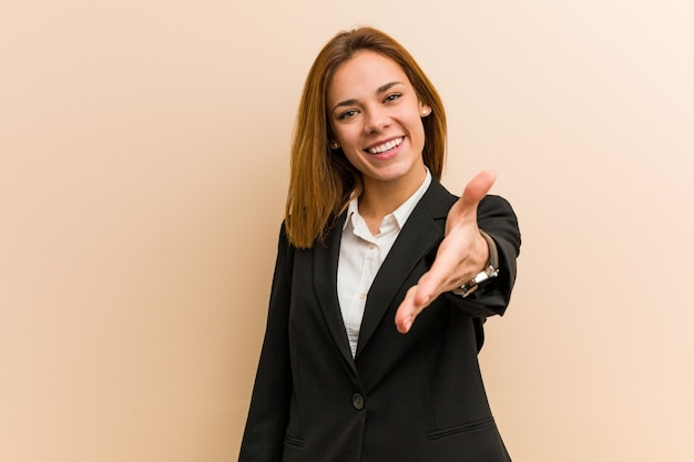 Young caucasian business woman stretching hand at camera in greeting gesture.