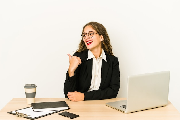 Young caucasian business woman working on her desktop isolated points with thumb finger away, laughing and carefree.