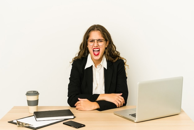 Young caucasian business woman working on her desktop isolated screaming very angry and aggressive.