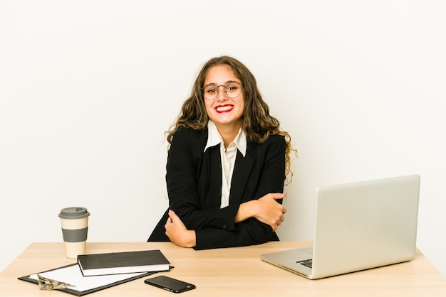 Young caucasian business woman working on her desktop isolated smiling.
