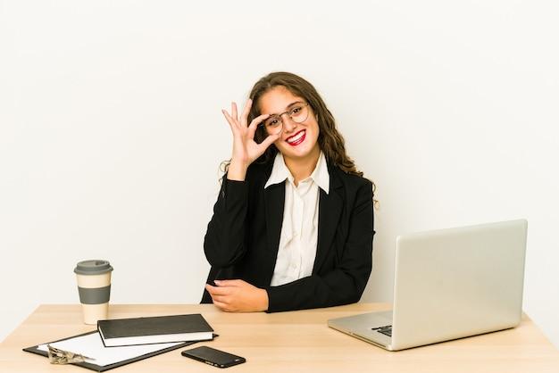 Молодая кавказская бизнес-леди, работающая на своем рабочем столе, изолировала возбужденный жест на глазах.