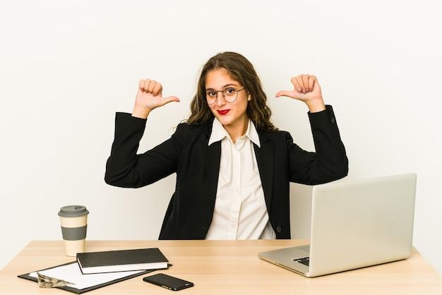 Молодая кавказская бизнес-леди, работающая на своем изолированном рабочем столе, чувствует гордость и уверенность в себе, пример для подражания.