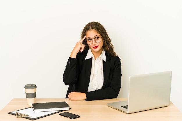 Молодая кавказская бизнес-леди, работающая на своем рабочем столе, изолировала указательный храм пальцем, думая, сосредоточившись на задаче.