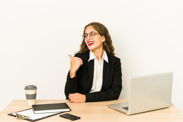 デスクトップで作業している若い白人ビジネスウーマンは、親指の指を離して、笑いながらのんきなポイントを分離しました。
