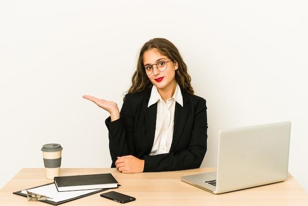 Молодая кавказская бизнес-леди, работающая на своем рабочем столе, показывающая пространство для копии на ладони и держащая другую руку на талии.