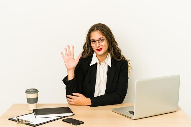 Молодая кавказская бизнес-леди, работающая на своем рабочем столе, улыбаясь, веселый показ номер пять с пальцами.
