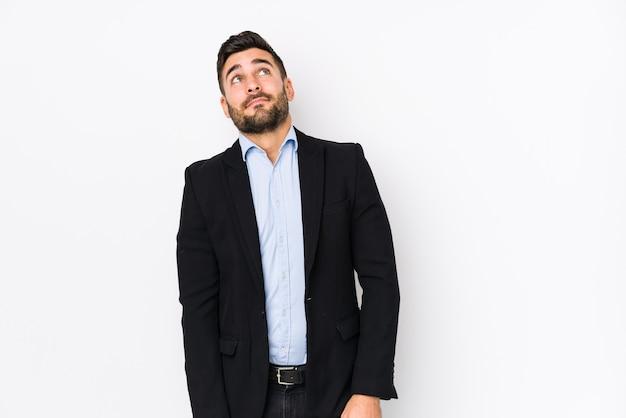 Молодой кавказский бизнесмен против белой стены изолировал мечтать о достижении целей и задач