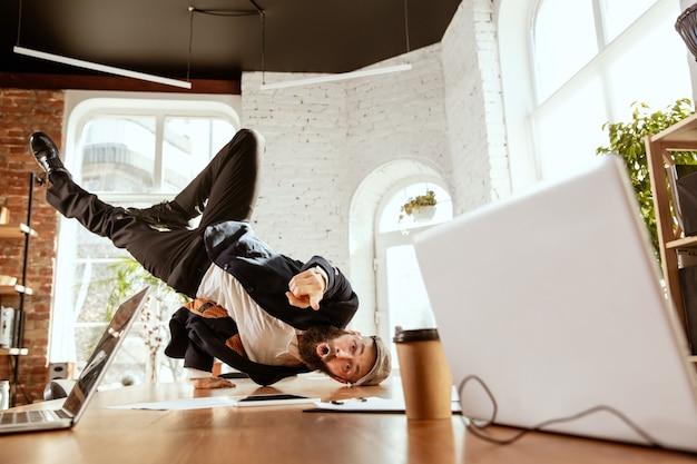 젊은 백인 사업가가 작업 시간에 현대적인 사무실에서 가제트를 들고 브레이크 댄스를 추며 즐거운 시간을 보내고 있습니다. 관리, 자유, 전문 직업, 대체 작업 방식. 그의 일을 사랑합니다.