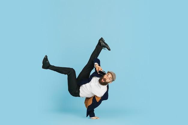 파란색 스튜디오 배경에서 댄스 브레이크 댄스를 즐기는 젊은 백인 사업가