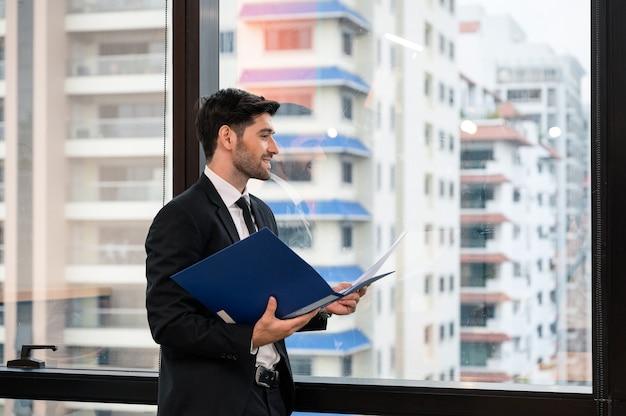 笑みを浮かべて、近代的なオフィスの窓から見ていると金融ドキュメントを保持している若い白人実業家