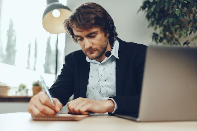 クライアントパートナーとのビデオ通話を保持している若い白人実業家