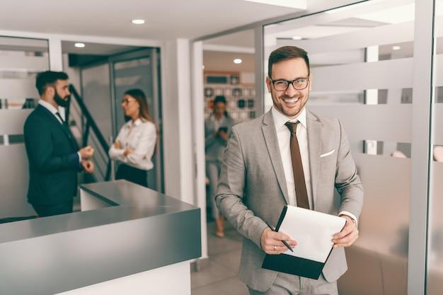 フォーマルな服装と廊下に立っている間彼の手でクリップボードでポーズの眼鏡の若い白人実業家。バックグラウンドでの同僚のチャット。