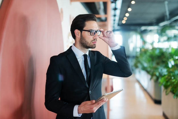 片方の手でタブレットを保持し、もう片方の手で眼鏡をかけるフォーマルウェアの若い白人実業家。 Premium写真
