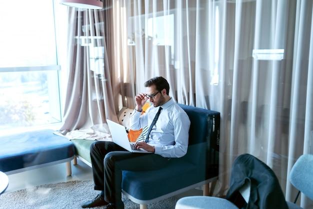 フォーマルな服装でオフィスのソファーに座っていると仕事にラップトップを使用して若い白人実業家。