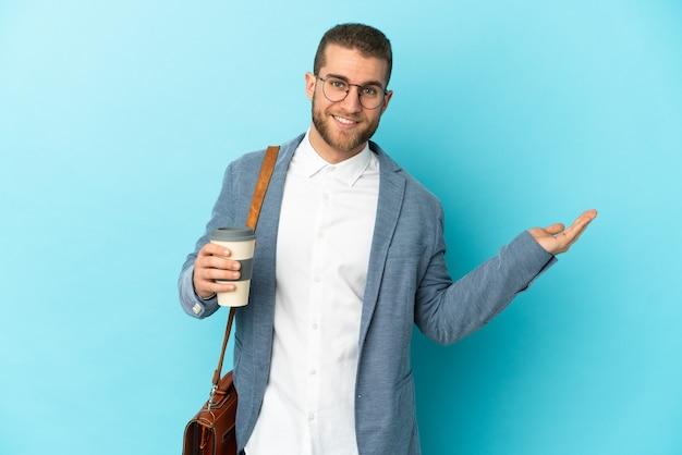 青い背景に孤立した若い白人実業家は、来て招待するために手を横に伸ばします