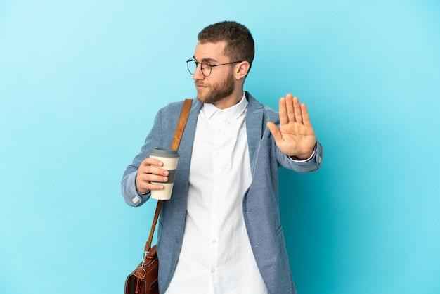 Молодой кавказский бизнесмен изолирован на синем фоне, делая жест стоп и разочарованный