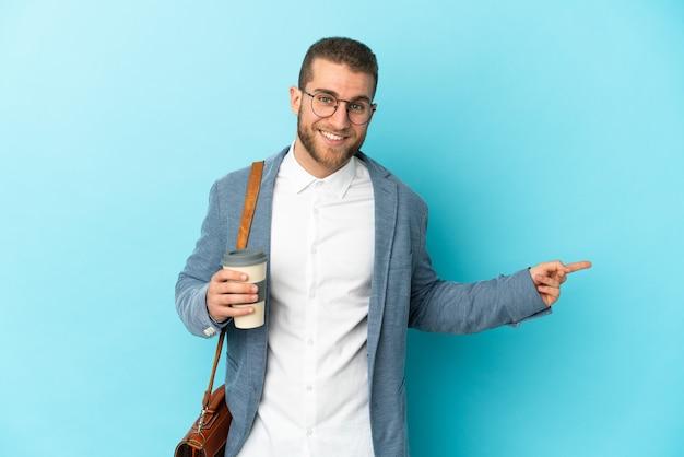 横に指を指している青い背景に分離された若い白人実業家