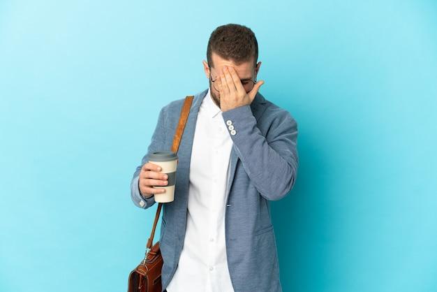Молодой кавказский бизнесмен изолирован на синем фоне с усталым и больным выражением лица