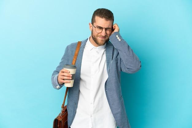 欲求不満と耳を覆っている青い壁に孤立した若い白人実業家