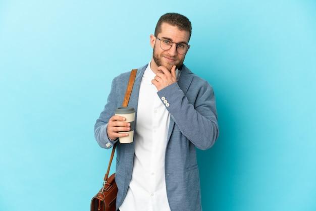 측면을 찾고 웃 고 파란색 벽에 고립 된 젊은 백인 사업가